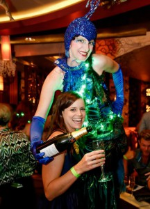 Madam Peacock Stilt Walker serving champagne