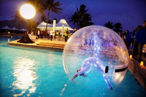 acrobat performs inside a giant inflated bubble that floats on the surface of the pool